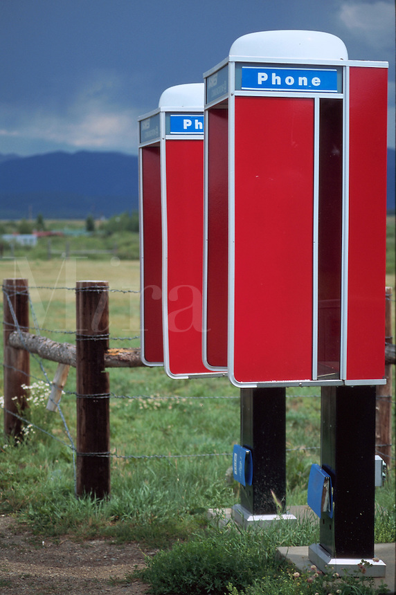 Bright red telephone kiosks in a rural meadow under a stormy summer sky. Colorado.