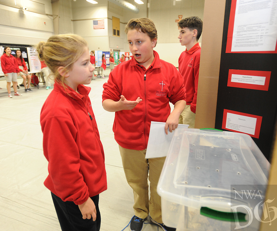 NWA Democrat-Gazette/ANDY SHUPE<br /> Murphy Beck (center), 13, a seventh-grader at St. Joseph Catholic School, explains his study of environmental preference of cockroaches Thursday, Feb. 9, 2017, as Kyliee James, 9, a fourth-grader, listens while participating in the school's science fair at the school in Fayetteville. Sixth- through eighth-graders at the school took part in the fair with a chance to compete in the Northwest Arkansas Regional Science and Engineering Fair March 3 at the University of Arkansas.