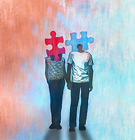 Young couple holding hands with matching jigsaw puzzle piece heads