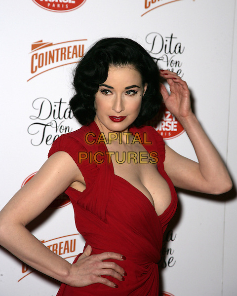 DITA VON TEESE .Opening Night at MGM Grand's Crazy Horse Paris inside the MGM Grand Resort Hotel and Casino, Las Vegas, Nevada, USA, 31st March 2010..half length hand on hip touching hair make-up beauty hair lipstick  red  low cut cleavage shoulder pads dress .CAP/ADM/MJT.©MJT/Admedia/Capital Pictures