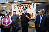 Pictured: A Dyfed Powys Police officer address the protesters gather outside Pembroke police station, west Wales, UK. Thursday 13 July 2017<br /> Re: Angry protesters staged a six-hour demonstration through the night after concerns a convicted criminal was living in their community.<br /> Crowds of people chanting and setting fire to bins gathered in Gwilliam Court, in Monkton, Pembrokeshire, at 9.30pm on Tuesday.<br /> Police were called and took two people from a property before the disturbance ended six hours later.<br /> On Wednesday, about 100 protesters gathered outside a council office.<br /> The crowd outside the office in Argyle Street, Pembroke Dock, were shouting and chanting about the situation in Monkton, with some saying they were not leaving until they had answers.<br /> Dyfed-Powys Police said officers were present and &quot;engaging with the community about their concerns&quot;.