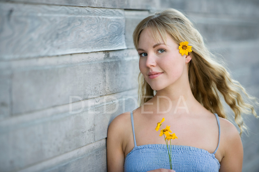 A beautiful blond young woman stands outdoors with flowers in her hair in the summer.