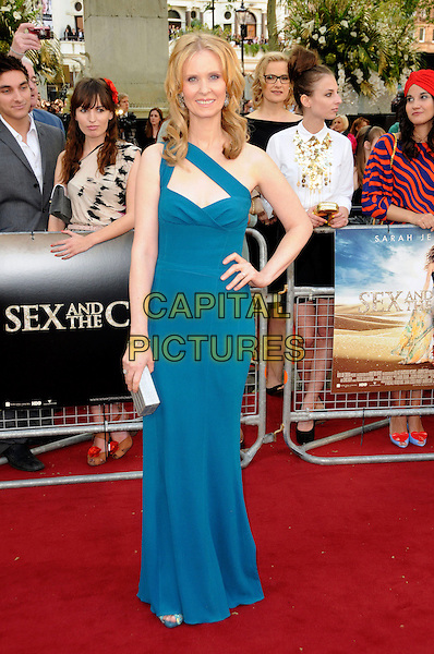 """CYNTHIA NIXON .in Narciso Rodriguez.Attending the """"Sex And The City 2""""  UK film premiere, Odeon Leicester Square, London, England, UK, May 27th 2010..arrivals full length one shoulder straps blue teal dress hand on hip beige clutch bag long maxi .CAP/CAS.©Bob Cass/Capital Pictures."""