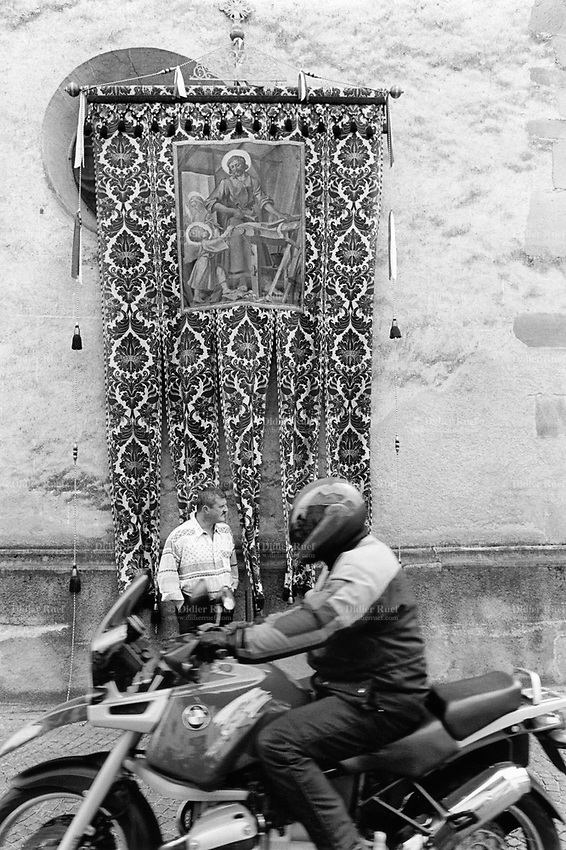 Italy. South Tyrol. Tisens. Religious procession on August 15 for the Assumption. A man waits on the sidewalk while a BMW motorbike passes on the road.<br /> A drawing of Joseph in his carpenter's shop with Mary and Jesus. Joseph is a figure in the Gospels, the husband of Mary, mother of Jesus, and is venerated as Saint Joseph in the Catholic Church. Christian tradition places Joseph as Jesus' foster father. The Assumption of the Virgin Mary into Heaven, often shortened to the Assumption, is also known as the Falling Asleep of the Blessed Virgin Mary, According to the beliefs of the Catholic Church was the bodily taking up of the Virgin Mary into Heaven at the end of her earthly life. The Assumption is a major feast day, commonly celebrated on August 15th. The feast is marked as a Holy Day of Obligation in the Roman Catholic Church. South Tyrol (German: S&uuml;dtirol; Italian: Sudtirolo, also known by its alternative Italian name Alto Adige) is an autonomous province in northern Italy. 15.08.1999 &copy; 1999 Didier Ruef