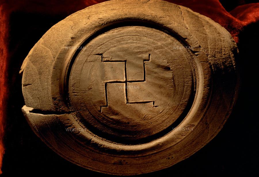 """Musée de Khotan. Bol en bois gravé d'une Svastika, symbole religieux de l'Inde vedique, lie au culte de Mithra. Sous un bol de bois expose au Musee de Khotan, le signe du mithraisme montre l'importance du culte Mithra dans cette region. Cette religion indo-iranienne vénère le dieu Mithra, """"le dieu de la lumière, assimilé au soleil"""". Les ruines de Niya, comme il est convenu maintenant d'appeler cet ensemble archéologique, sont dispersées sur une cinquantaine de kilomètres carrés et s'articulent autour d'un sanctuaire bouddhiste dont les alentours sont jonchés d'ossements humains qui quelquefois affleurent à la surface du sol. Tout laisse à supposer que d'autres ruines, qui seraient celles d une cite beaucoup plus importante, sont encore enfouies dans les sables. On devine des marques qui pourraient etre celles d anciens remparts, peut etre des fondations de temples. Khotan Museum. On the bottom of a wooden bowl, the sign of Mithraism shows the importance of the cult of Mithra in the region. This Indo-Iranian religion worships the god Mithra, defined as """"a god of light, assimilated to the sun"""". Niya's ruins, as it has been decided to call this archaeological corpus, are spread over 50 km2 and articulate themselves around a Buddhist sanctuary of which the surroundings are full of human bones that sometimes rise to the ground's surface. Everything leads us to believe that other ruins, belonging to a much greater city, are still buried in the sands. We distinguish traces of what could have been ramparts or maybe the foundations of temples."""