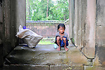 A Cambodian girl rests from gathering water bottles while taking shelter from the rain at Angkor Wat in Siem Reap. Gathering plastic bottles for recycling is one of the ways that young children make a meagre living.