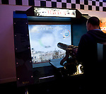 Man playing shooting video game in an amusement arcade, Weymouth, Dorset, England