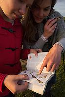 Rita Norvaisaite, from the Baltic Environmental Forum, helps a yoiung girl find the right bird in a bird book, during a bird festival in the Nemunas River Delta, Lithuania