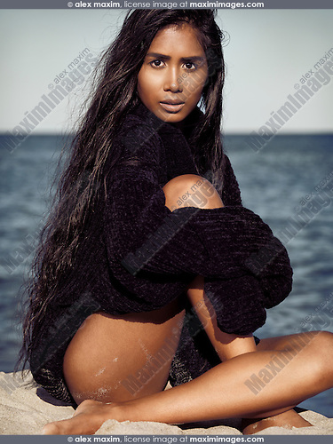 Beautiful young woman with long dark hair wearing a black turtleneck sweater sitting on sand at the beach