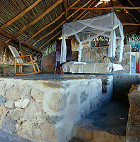 Built on two levels this guest wing has a bedroom with a stone floor under a open palapa roof