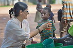 Sister Raquel Peralta, a Catholic nun from Paraguay, gives a girl of cup of water in a camp for more than 5,000 displaced people in Riimenze, in South Sudan's Gbudwe State, what was formerly Western Equatoria. Families here were displaced at the beginning of 2017 as fighting between government soldiers and rebels escalated.<br /> <br /> Peralta is a member of the Missionary Sisters Servants of the Holy Spirit, and works in South Sudan as part of Solidarity with South Sudan, an international network of Catholic groups working in the newly independent country. Solidarity and Caritas Austria have both supported efforts by the diocese to ensure that the displaced families here have food, shelter and water.