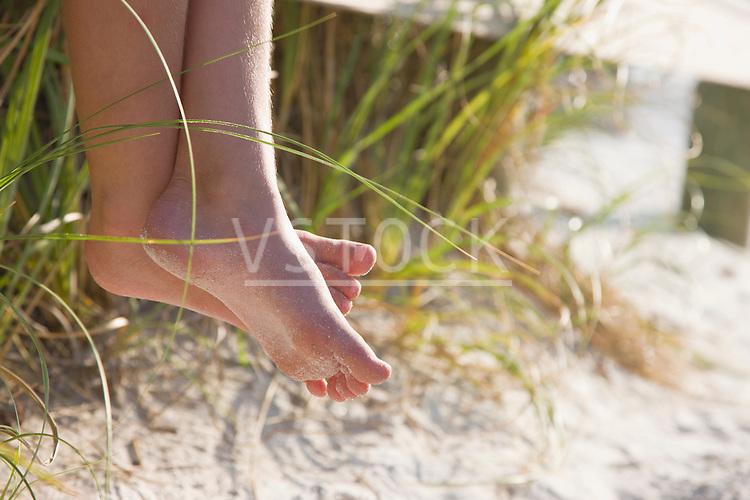 USA, Florida, St. Pete Beach, Bare feet of girl (8-9) sitting on rail on beach