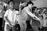 Children of Bassac. Assistant Master Nop Thyda is helping a young student to learn the right moves.  Repeat, repeat, repeat the same moves again and again. Repeat to get to the perfection. Nop Thyda is a strict teacher loved by her students. Born in 1973, she survived the Khmer Rouge regime (1975-1979) and despite her young age at this time remembers « the smell of death lingering in the air at night ». She's actually a researcher for the Department of Performing Arts and an expert of traditional Yke opera. She's a a dance instructor for the dancers of the slum since 2005. Phnom Penh, Cambodia - 2005