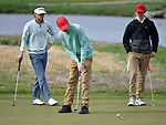 Ritenour golfer Zach Bohmer (center) putts at the 13th hole as he's watched by Webster Groves golfer Charlie Scheipeter (left) and Kirkwood golfer Joe Avery. Golfers in Suburban Central and Suburban XII Conference schools competed in a tournament at the Gateway National Golf Course in Madison, Illinois on Wednesday April 25, 2018.  Tim Vizer | Special to STLhighschoolsports.com