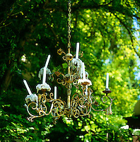A rustic wrought-iron chandelier with a new set of candles hangs from a tree in the garden