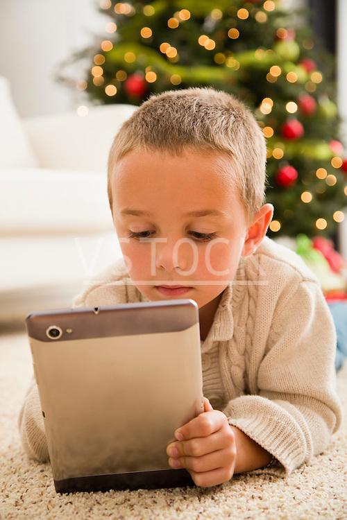 Boy (6-7) using digital tablet lying on carpet