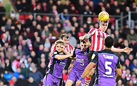 Lincoln City's Harry Anderson gets above Port Vale's Mitchell Clark, left, and Leon Legge to win a header<br /> <br /> Photographer Andrew Vaughan/CameraSport<br /> <br /> The EFL Sky Bet League Two - Lincoln City v Port Vale - Tuesday 1st January 2019 - Sincil Bank - Lincoln<br /> <br /> World Copyright &copy; 2019 CameraSport. All rights reserved. 43 Linden Ave. Countesthorpe. Leicester. England. LE8 5PG - Tel: +44 (0) 116 277 4147 - admin@camerasport.com - www.camerasport.com
