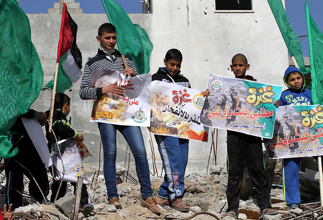 Palestinian children hold placards on the rubbles of destroyed houses during a protest against the United Nations decision to suspend payments for Palestinians, whose houses were damaged during a 50-day war last summer, in Beit Hanoun in the northern Gaza Strip January 30, 2015. The main U.N. aid agency in the Gaza Strip said on Tuesday a lack of international funding had forced it to suspend payments to tens of thousands of Palestinians for repairs to homes damaged in last summer's war. Photo by Mohammed Asad