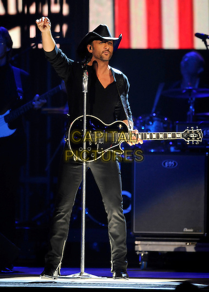 TIM McGRAW.performs during the 43rd Annual CMA Awards, Country Music's Biggest Night, held at the Sommet Center, Nashville, Tennessee, USA, 11th November 2009. live show on stage full length concert gig music  microphone hand arm raised up guitar cowboy hat black .CAP/ADM/LF.©Laura Farr/AdMedia/Capital Pictures.