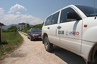 Car caravan led by a USAid four wheel drive car Poshnje Albania, Balkan, Europe.