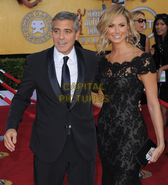 George Clooney and Stacy Keibler.18th Annual Screen Actors Guild Awards held at The Shrine Auditorium, Los Angeles, California, USA..January 29th, 2012.SAG SAGS half length dress lace off the shoulder couple clutch bag black suit white shirt tie clutch bag.CAP/RKE/DVS.©DVS/RockinExposures/Capital Pictures.