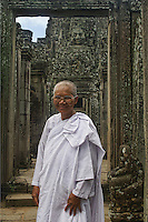 In her white robes, this beautiful Bhikkhuni (female monk) stands in front of one of the many doorways in Angkor Thom through which you can see one of the stone faces for which Angkor Thom is famous. Angkor Thom is one of the temples in the Angkor Wat Archelogical Park in Cambodia.