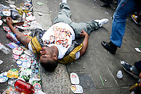 General News: A man lies unconcious umong empty cans of beer on the street of Westbourn Park Road after being bottled at Notting Hill Carnival, London. The largest festival of its kind in Europe was largely peaceful, however some use the three day event as a ground for gang fighting.