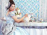 Beautiful smiling asian lady in a luxurious blue dress hosting a tea party.