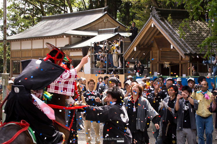 A rider throws confetti after attempting a ride at the Tado Horse Festival.