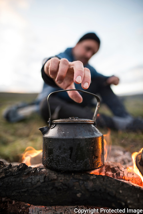 Mann koker kaffe på bålet. ---- Coffe pot on capm fire.