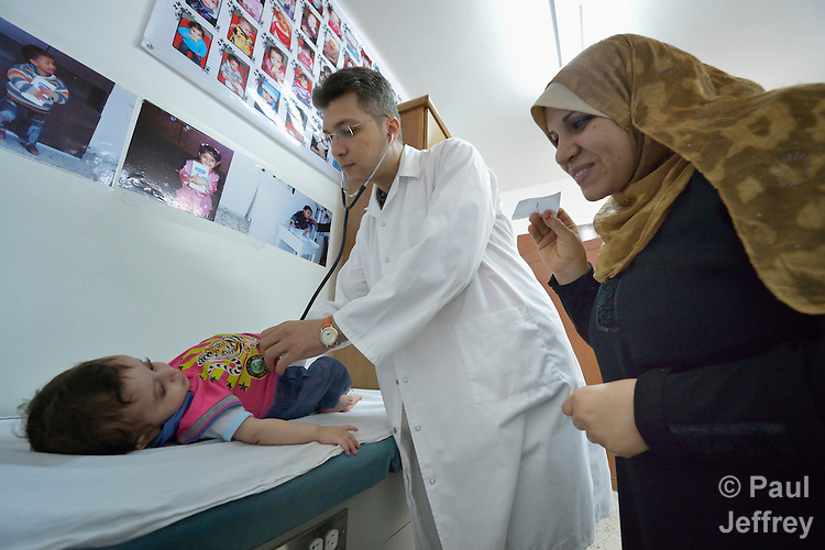 As the mother attempts distraction, Dr. Mohi El Sharqawi examines a child in the pediatric department of the Al Ahli Arab Hospital in Gaza City. The Anglican Church-affiliated hospital is a member of the ACT Alliance.<br /> <br /> The 2014 war provoked serious damage to Gaza's health infrastructure. Seventeen hospitals, 56 primary health care facilities and 45 ambulances were damaged or destroyed. Sixteen health care workers were killed and 83, most of them ambulance drivers and volunteers, were injured. <br /> <br /> Parental consent obtained.
