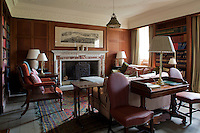 Sofas and antique chairs face a marble fireplace in the panelled library