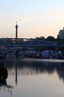 Paris Right Bank: A view of the port de l&rsquo;Arsenal in Paris (it links the Canal de Saint Martin to place de la Bastille), with its boats, its typical bridge, and the column of July that reflects itself onto the flat water surface on the background, in the sunrise light.<br />
