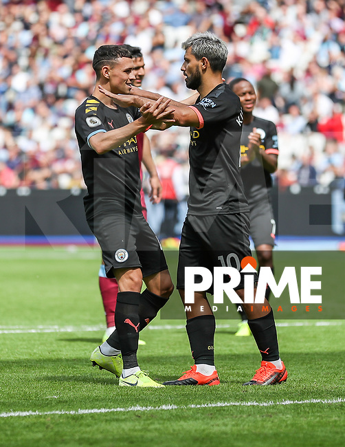 GOAL - Sergio Aguero of Manchester City (10) celebrates with Phil Foden of Manchester City (left) after he scores from the penalty spot to make the score 0-4 during the Premier League match between West Ham United and Manchester City at the London Stadium, London, England on 10 August 2019. Photo by David Horn.