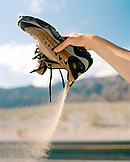 USA, California, woman's hand pouring sand out of shoe, Death Valley National Park