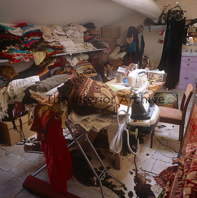 A work room with a work table with a sewing machine. An ironing board and iron and piles of various fabrics stored on shelves.