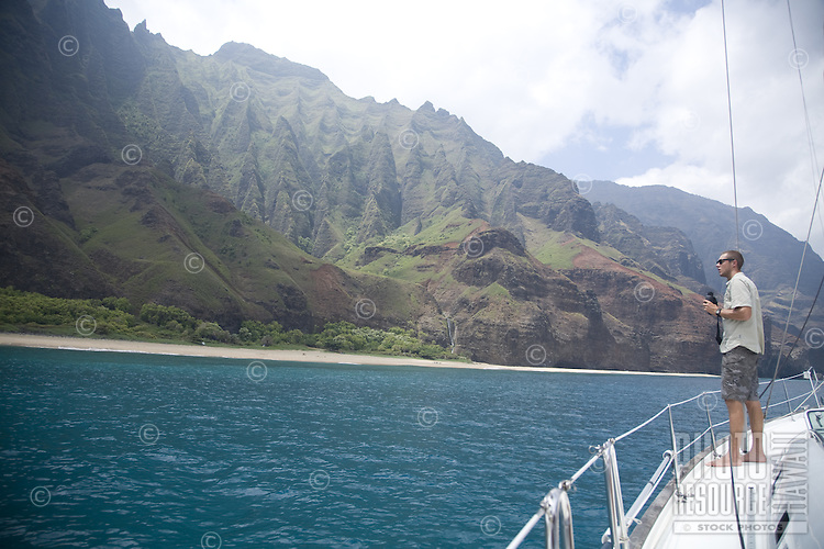 Young man on sailboat off of Kalalau Beach on Kauai's Na Pali coast