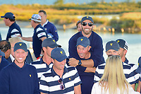 Dustin Johnson (USA) hops on the back of Matt Kuchar (USA) before the team photo following the 2017 President's Cup, Liberty National Golf Club, Jersey City, New Jersey, USA. 10/1/2017. <br /> Picture: Golffile | Ken Murray<br /> <br /> All photo usage must carry mandatory copyright credit (&copy; Golffile | Ken Murray)