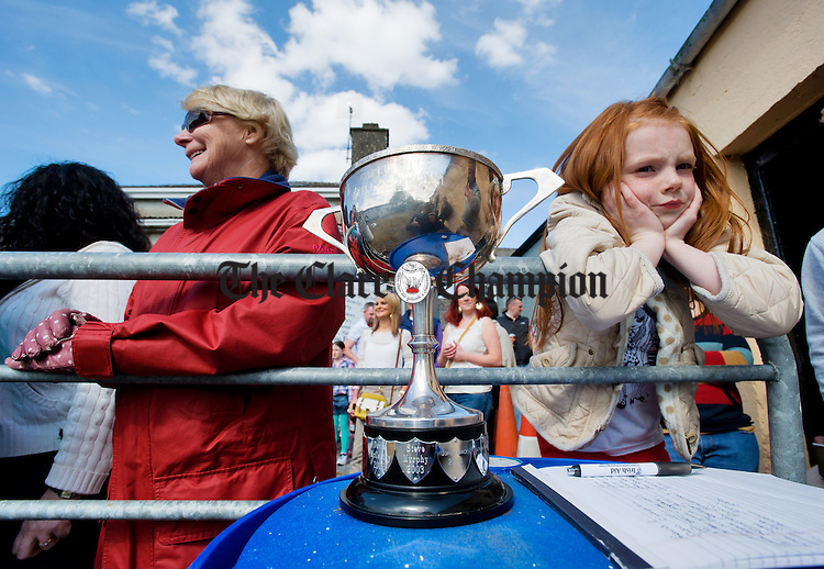 Katie Lee, right, daughter of last years champion Dean Lee, keeps an eye on the silverware at the World Stone Throwing Championships in Corofin. Photograph by John Kelly.