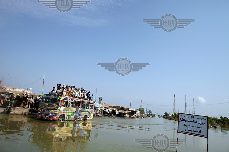 A bus carries lots of people as it passes through the floodwaters in the village of Sultan Kot. Severe flooding had left at least 1,600 people dead and affected up to 20 million.