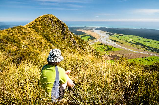 Young woman enjoying views from Mt. Fox toward Tasman Sea, Westland Tai Poutini National Park, UNESCO World Heritage Area, West Coast, New Zealand, NZ