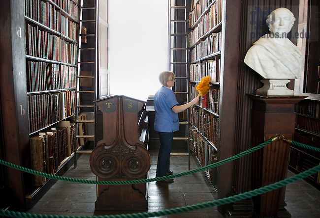 August 31, 2012; A woman dusts books on the shelves in the Long Room at Trinity College Library in Dublin, Ireland. Hesburgh Libraries Advisory Council took a private tour to see the Book of Kells and the Long Room.  Photo by Barbara Johnston/University of Notre Dame