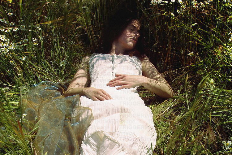 A girl in a white dress, sleeping among camomiles and plants on a summer meadow.