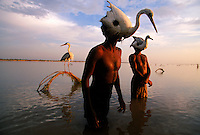 Bird Hunters in Indus River.The Indus river valley leaves some surprising remnants of it's culture.  A stone's throw from the largest intact Harappan Site (Mohenjo Daro), these hunters use the same method they used to hunt birds that goes back to 3300BC.  They tie their decoy live birds to hoops in the middle of the river and drop into the river so only their bird covered heads are showing.  When a bird lands they wiggle their heads as if they are a bird swimming and then physically grab their prey.  4,800 years ago, at the same time as the early civilizations of Mesopotamia and Egypt, great cities arose along the flood plains of the Indus and Saraswati (Ghaggar-Hakra) rivers.  Developments at Harappa have pushed the dates back 200 years for this civilization, proving once and for all, that this civilization was not just an offshoot of Mesopotamia..They were a highly organized and very successful civilization.  They built some of the world's first planned cities, created one of the world's first written languages and thrived in an area twice as large as Egypt or Mesopotamia for 900 years (1500 settlements spread over 280,000 square miles on the subcontinent)..There are three major communities--Harappa, Mohenjo Daro, and Dholavira. The town of Harappa flourished during this period because of it's location at the convergence of several trade routes that spanned a 1040 KM swath from the northern mountains to the coast.