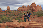 Family with baby walking in Arches National Park, Moab, Utah, USA. .  John offers private photo tours in Arches National Park and throughout Utah and Colorado. Year-round.