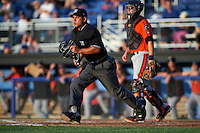 Umpire Jhonatan Biarreta gets into position as catcher Jerry McClanahan (19) looks on during a game between the Aberdeen IronBirds and Batavia Muckdogs on July 15, 2016 at Dwyer Stadium in Batavia, New York.  Aberdeen defeated Batavia 4-2.  (Mike Janes/Four Seam Images)