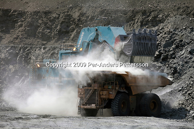 JWANENG, BOTSWANA - SEPTEMBER 24: Heavy vehicles load ore in the pit at Jwaneng, the richest diamond mine in the world on September 24, 2009 in Jwaneng, Botswana. It's owned by Debswana, a partnership between the De Beers Company and the government of Botswana. The mine employs about 3000 people and is also processing ore for the mine as well as two of Debswana's other mines. The truck can carry about 245 tons of ore each time. The mine operates 24 hours a day, all year around. Diamond wealth has brought lots of revenues to Botswana, including an impressive infrastructure such as roads and free education up to university. (Photo by Per-Anders Pettersson)...