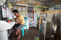 At the APDS association's premises, Suriadi, 29 years old, takes care of production. He checks the honey's quality and also monitors the dehydrating process that lowers the honey's moisture content from 27% to 21%, an indispensable step that prevents rapid fermentation and thus allows for the marketing of the honey. APDS produced 18 tons of honey in 2014 in the territory covered by six villages.///Dans les locaux de l'association APDS, Suriadi, 29 ans, s'assure de la production. Il contrôle la qualité du miel et suit également le processus de déshumidification qui permet d'abaisser son taux d'humidité du miel de 27 % à 21 %, une étape indispensable pour éviter une fermentation rapide et permettre ainsi sa commercialisation. APDS a produit 18 tonnes de miel en 2014 sur le territoire de six communes.