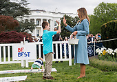 "A child ""high fives"" First Lady Melania Trump during the White House Easter Egg Roll at the White House in Washington, D.C. on April 22, 2019. <br /> Credit: Kevin Dietsch / Pool via CNP"