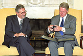 United States President Bill Clinton looks at an album as he hosts a working visit with President Emil Constantinescu of Romania in the Oval Office of the White House in Washington, DC on Thursday, July 16, 1998.<br /> Credit: Ron Sachs / CNP